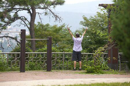 A Korean man stretches during an exercise routine near Seoul, Korea  photo