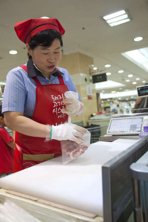 Woman packages beef at a Korean grocery store in Seongnam, Korea.