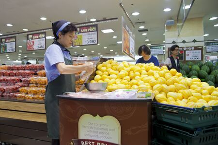A Korean woman slices up fruit for customers to sample in Seongnam, Korea. Stock Photo - 14905130