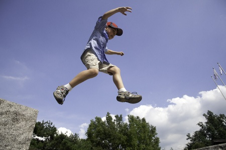 A young boy leaps off a large rock and is in mid air against the blue sky  photo