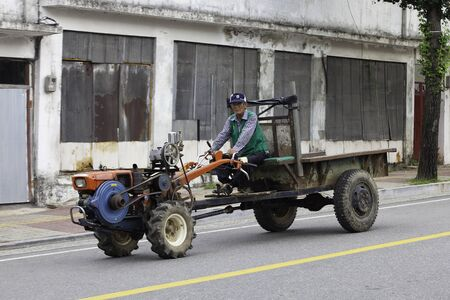 Chunchon, Korea - July 28, 2012. A Korean man drives an old traditional type tractor though a rural area.