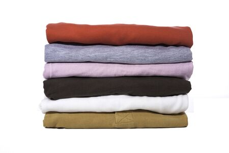 heap: A stack of folded shirts against a white background. Stock Photo