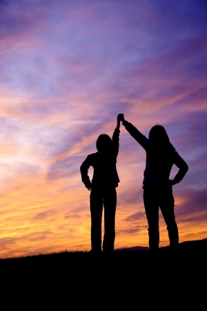triumph: A mother and daughter holding raised hands watch the sunset