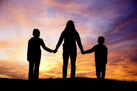 A woman and her son and daughter watch the pretty sunset Stock Photo - 15584885