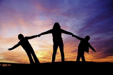 Una madre sostiene a sus dos hijos mientras juegan en la puesta del sol Foto de archivo - 15584888