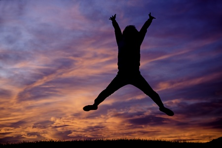 liveliness: Jumping up into the air at sunset with orange clouds