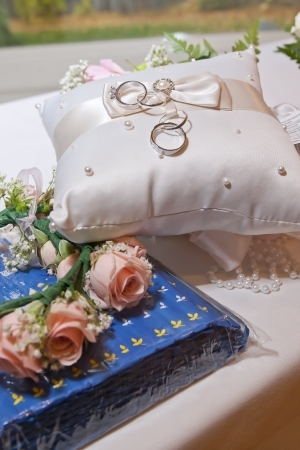 A pair of wedding rings sit on a pillow next to pink roses. Stock Photo - 16233811