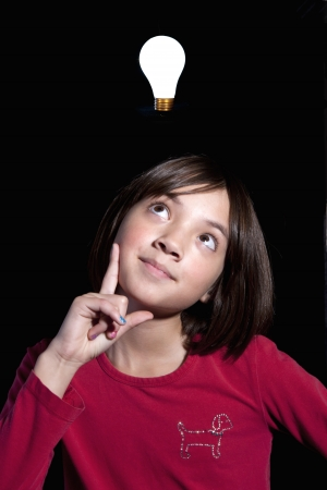 A young girl has a lightbulb moment in this concept image  photo