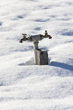 double headed: A double headed water faucet rises out of the snow