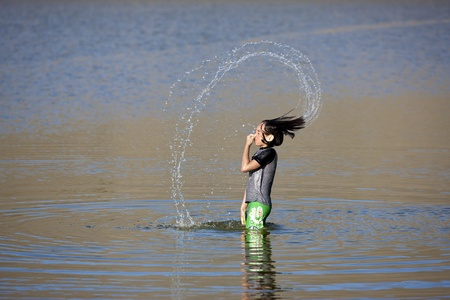 whipping: Girl makes pattern with water    Stock Photo
