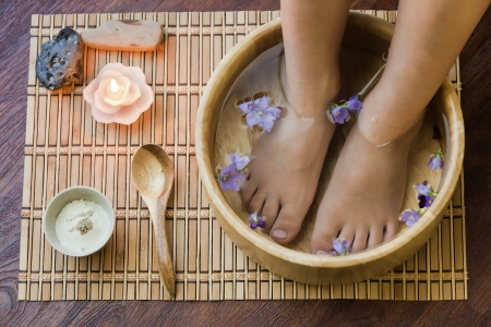 Soaking feet in wooden bowl