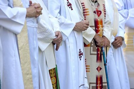 religion catolica: Los sacerdotes con las manos juntas