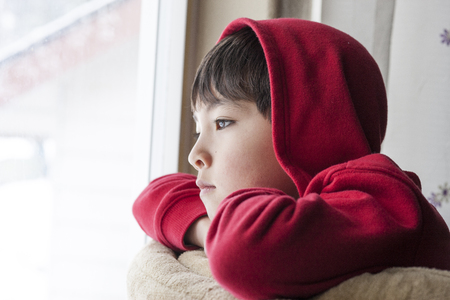 A young boy appears to be bored and stuck indoors.