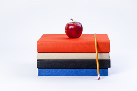 Apple on books and pencil  photo