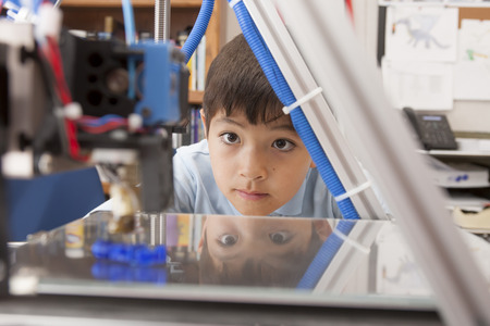 Boy watches machine intently  Imagens