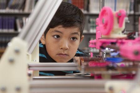 Boy watches printer in action