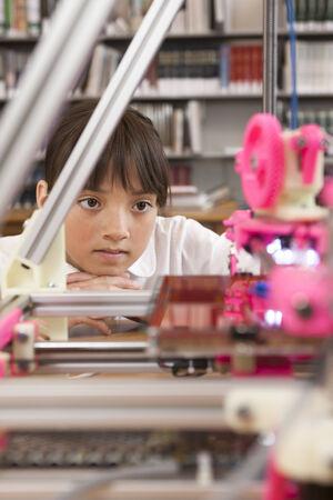 Girl looking at 3D printer
