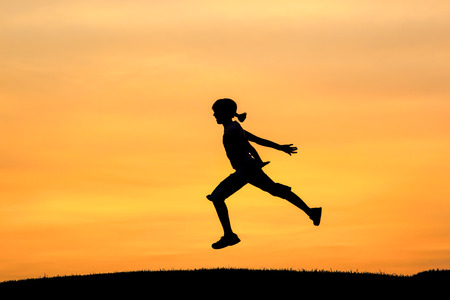 Girl leaps during sunset