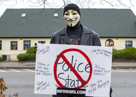 Spokane, Washington USA- December 20, 2014. A protestor in a Guy Fawkes mask displays a sign at a rally in Spokane Valley, Washington.