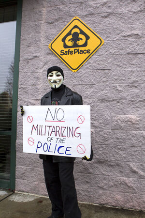 guy fawkes mask: Spokane, Washington USA- December 20, 2014. A protestor in a Guy Fawkes mask displays a sign at a rally in Spokane Valley, Washington.