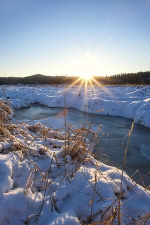 Sun rays over winterscape in Hauser, Idaho. Banco de Imagens