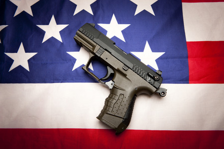 amendment: A concept image of liberty showing a pistol  on the American flag, Stock Photo