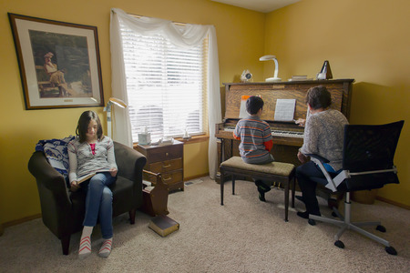 piano lesson: Older sister waits for her younger brother to finish piano lesson. Editorial