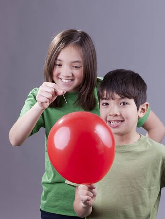 Popping her brothers balloon. Stock Photo