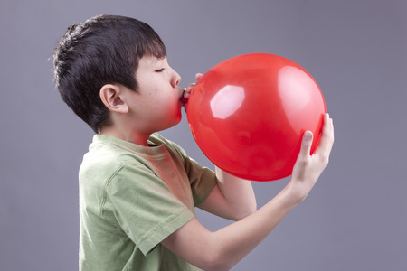 Boy blows up balloon.