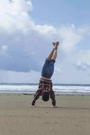 Boy does handstand on the beach in Newport, Oregon. photo