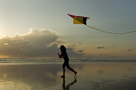 kites: Flying a kite at sunset on the beach in Newport, Oregon. Stock Photo