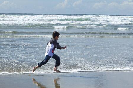 Boy runs on beach in Newport, Oregon. photo