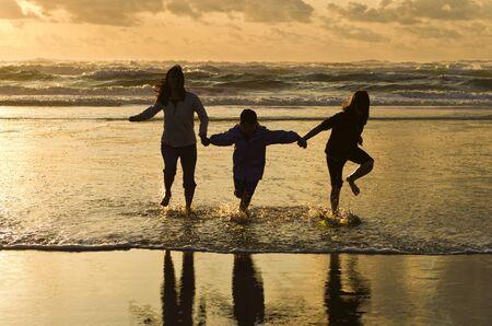 silueta hombre: Familia ejecuta en la playa al atardecer en Newport, Oreg�n.