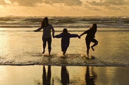 female silhouette: Family runs in the surf at sunset in Newport, Oregon.