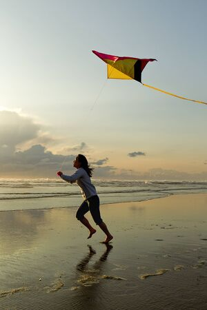 flying a kite: Woman with kite at beach in Newport, Oregon. Stock Photo