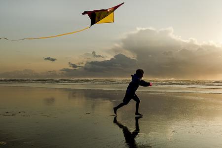 Jongen met Vlieger bij zonsondergang op het strand in Newport Oregon. Stockfoto