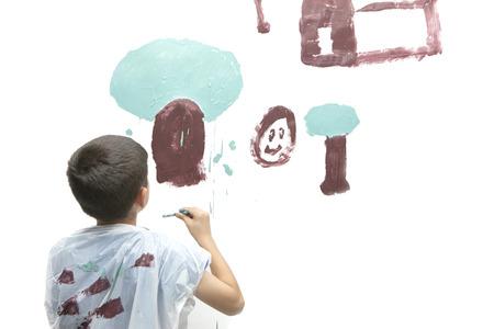 paints: Boy paints picture.