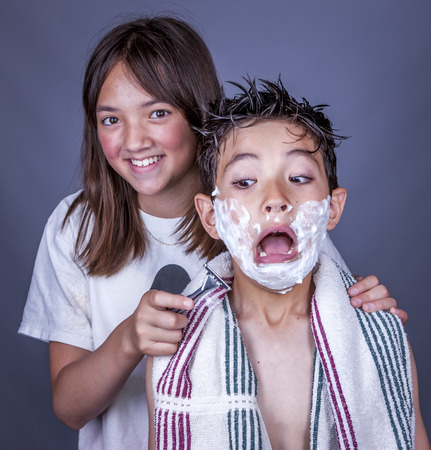 clowning: Siblings clowning with razor and cream. Stock Photo