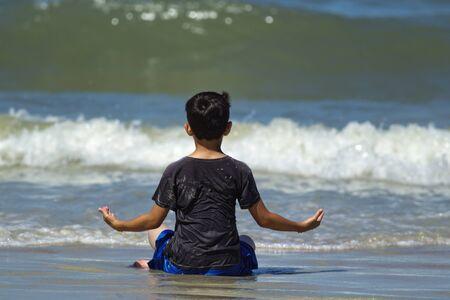 Boy meditates on the beach near Daytona Beach, FL. Stock fotó