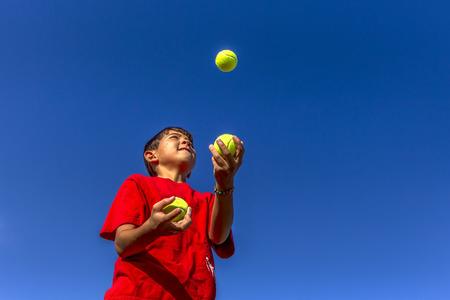 Young boy juggles balls.