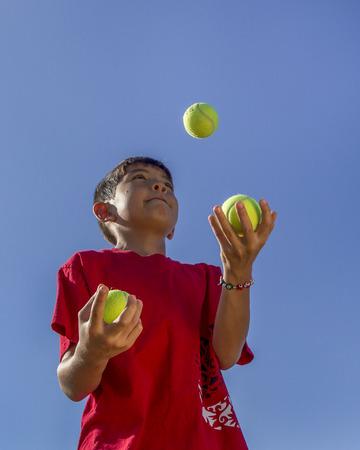 Boy juggles tennis balls.