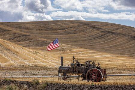 colfax: Steam engine and flag in field in Colfax, Washington.