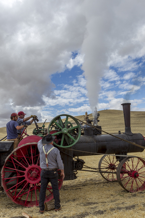 colfax: Men working on a steam engine at the old fashioned threshing bee in Colfax, Washington. Editorial