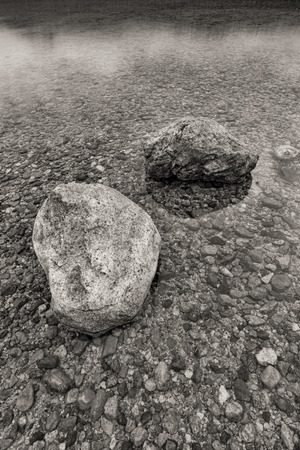 bw: BW of boulders in shallow water. Stock Photo