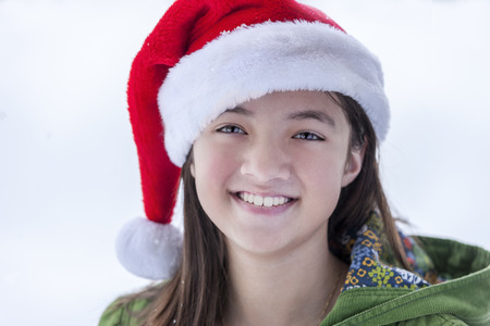 A young teen girls dons a santa hat and a big smile. Reklamní fotografie