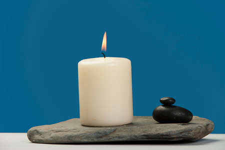 lit candle: Lit candle on a rock.