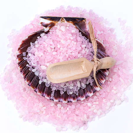 Pink bath salts and a wooden scoop insode of a seashell.