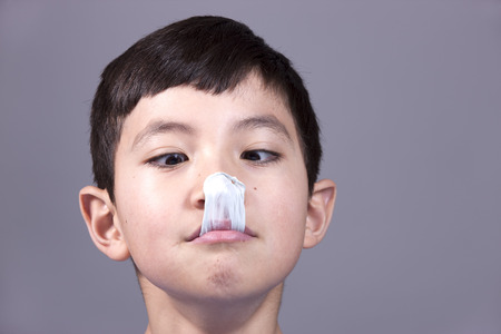 popped: Boy looks at popped gum on his nose. Stock Photo