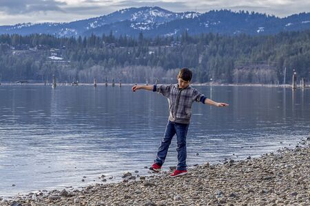 lakefront: Boy spins around by lakefront on Coeur dAlene Lake in Idaho.