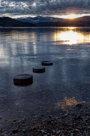 three objects: Three objects lead to setting sun on the Coeur dAlene Lake in north Idaho. Stock Photo